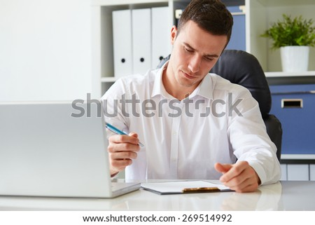 Young businessman signs a document at the office - stock photo