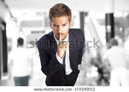 young businessman silence gesture in a company - stock photo