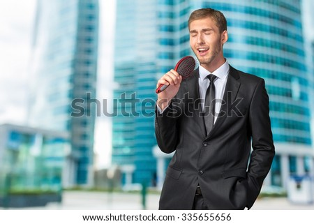 Young Businessman singing as if in microphone