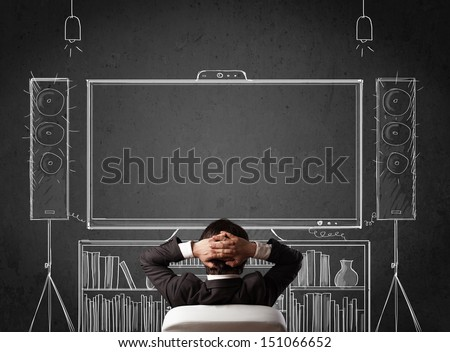 Young businessman sitting and enjoying home cinema system sketched on a chalkboard - stock photo