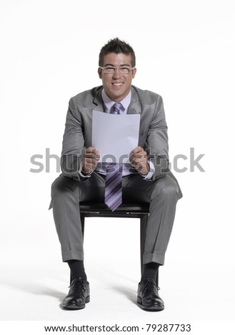 Young businessman sitting and reading a document on white background. - stock photo