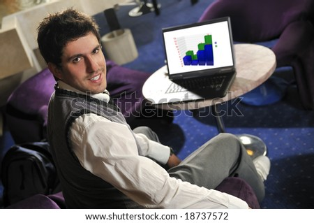 Young businessman sitting and working on business laptop - stock photo