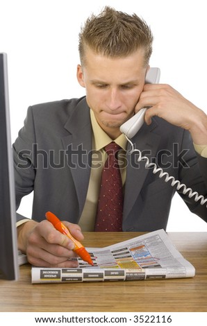 Young businessman sitting at desk, talking on phone and marking something in newspaper. White background, front view - stock photo