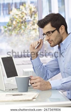 Young businessman sitting at desk, working with laptop computer, thinking. - stock photo