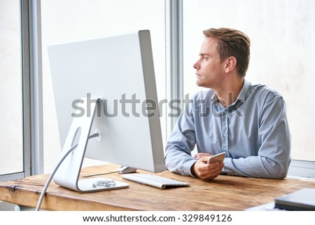 Young businessman sitting at his desk in a bright office with a large window holding his phone and looking away in deep thought - stock photo