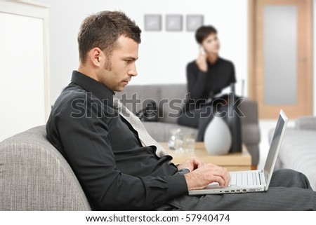 Young businessman sitting at office lobby working with laptop computer, smiling. - stock photo