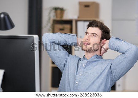 Young businessman sitting back in his chair at the office with his hand clasped behind his neck thinking and planning - stock photo