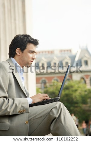 Young businessman sitting down with his laptop pc, working while outdoors in the city. - stock photo