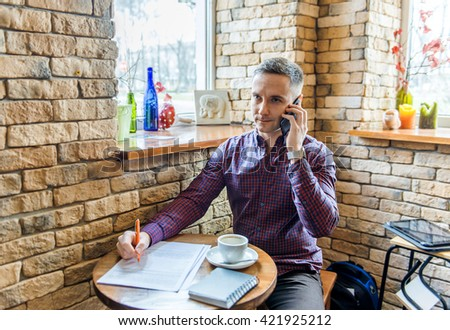 young businessman sitting in a cafe with documents, talking on the phone. - stock photo
