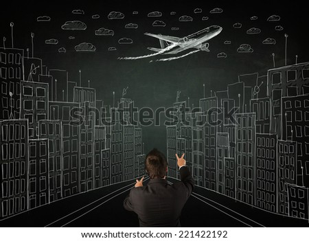 Young businessman sitting in an office chair and looking on a sketched cityscape drawing on a chalkboard - stock photo