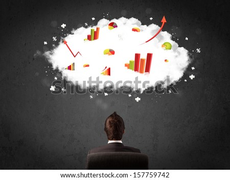 Young businessman sitting in an office chair with colorful charts in a cloud above his head - stock photo