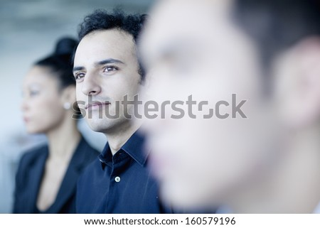 Young businessman sitting in business meeting with colleagues - stock photo
