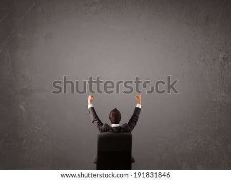 Young businessman sitting in office chair in front of a wall with empty space - stock photo