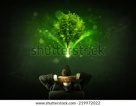 Young businessman sitting in office chair with a glowing tree and letters above his head - stock photo