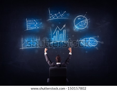 Young businessman sitting in office chair with glowing charts above his head - stock photo