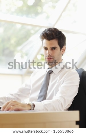 Young businessman sitting in office. Shallow focus. - stock photo