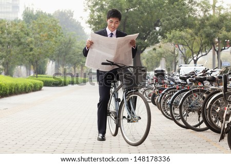 Young businessman sitting on a bicycle and reading the newspaper - stock photo