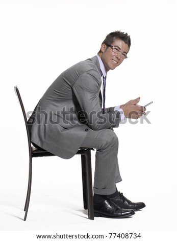 Young businessman sitting on a chair and using a mobile phone. - stock photo