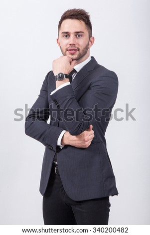 Young businessman sitting on a white background in a classic suit with his arms crossed.