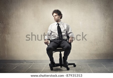 Young businessman sitting on an office chair - stock photo