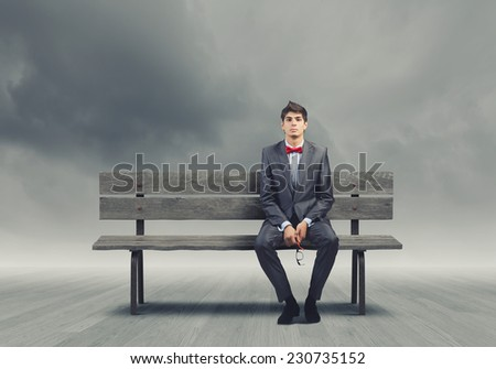Young businessman sitting on bench with glasses in hands