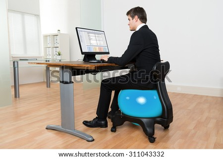 Young Businessman Sitting On Blue Pilates Ball While Working On Computer In Office - stock photo