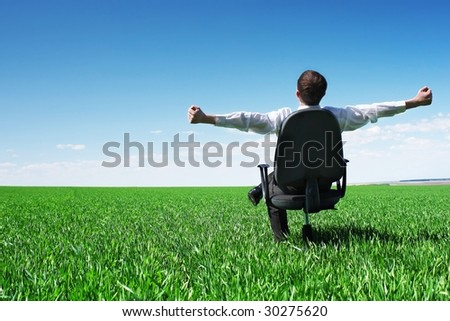 Young businessman sitting on chair in green field - stock photo