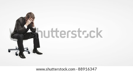 Young businessman sitting on chair with head down as if sad or depressed .Isolated on a white background - stock photo