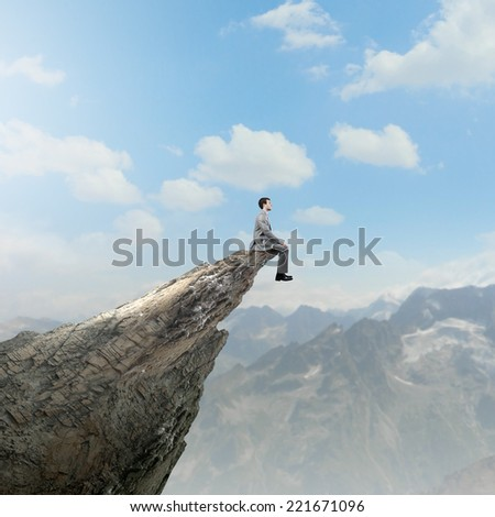 Young businessman sitting on edge of rock mountain - stock photo