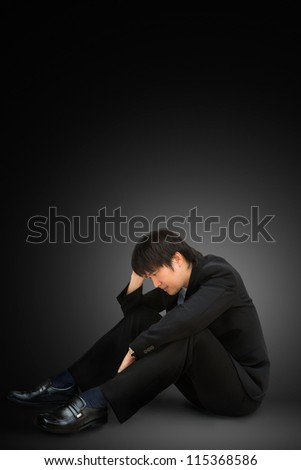 Young businessman sitting on floor with head down as if sad or depressed. - stock photo