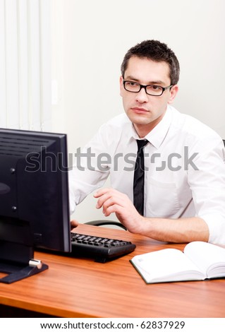 Young businessman sitting on his working place and looking at computer. Handsome man in glasses looking at computer's screen very seriously.