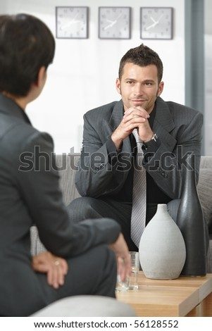 Young businessman sitting on sofa at office listening to talking businesswoman.