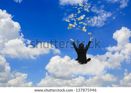 Young businessman sitting on the cloud with a lot of falling dollars - stock photo