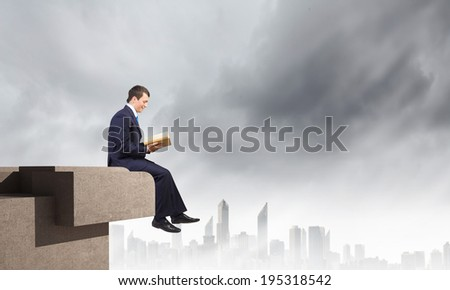Young businessman sitting on top of building and reading book