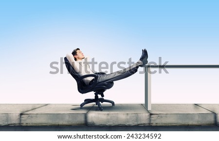 Young businessman sitting relaxed in chair with legs on table