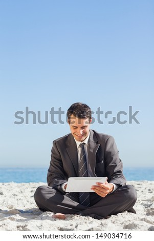 Young businessman sitting using his tablet computer on the beach