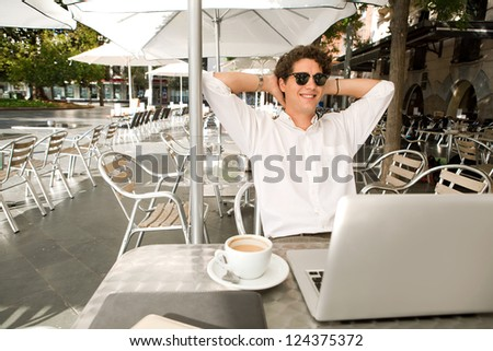 Young businessman sitting with his arms behind his head at a coffee shop while smiling with his laptop computer, outdoors. - stock photo