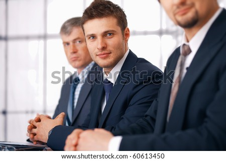 Young businessman sitting with his colleague at the meeting with crossed fingers. - stock photo