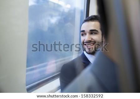 Young businessman smiling and looking out the window of subway - stock photo
