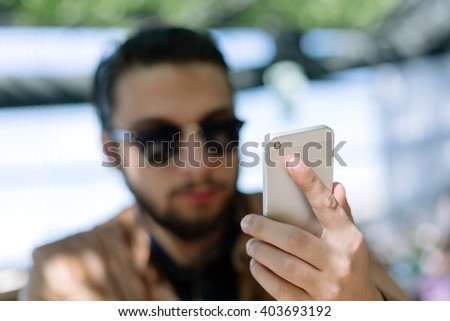 Young businessman smiling as he reads an sms on his mobile phone while taking a coffee break at the office