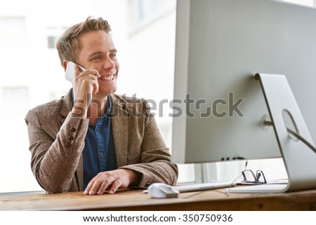 Young businessman smiling while having a conversation at his desk at work on his cellphone
