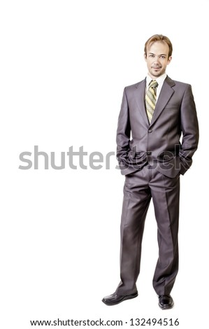 Young businessman smirks and keeps hands in pockets on white background - stock photo