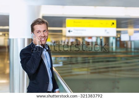 Young businessman speaking on the phone at the airport - stock photo