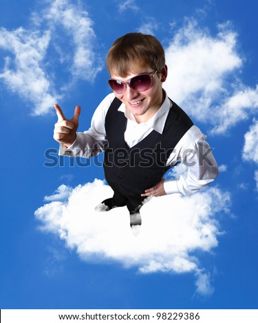 Young businessman standing against blue cloudy sky background