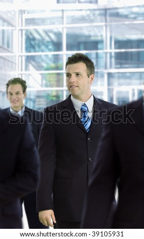 Young businessman standing among other businesspeople, in front of office building. - stock photo