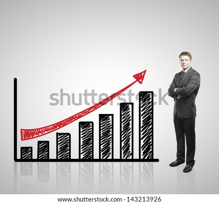 young businessman standing and drawing arrow graph - stock photo