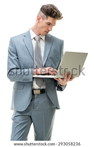 Young businessman standing and working at laptop. White background.