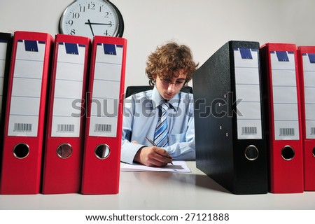 Young businessman standing at desk behind a stack of folders - stock photo