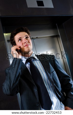 Young businessman standing at office lobby waiting for elevator and calling on mobile phone.