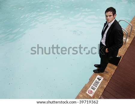 Young businessman standing at the edge of a pool. - stock photo